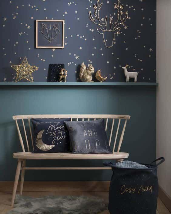 un coin romantique avec du papier peint étoile bleu marine et or, des étoiles et des figurines de lune et des oreillers assortis