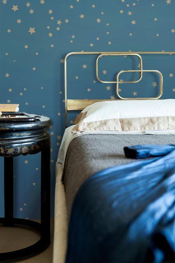 Un papier peint étoile bleu marine et doré et un lit doré avec une literie dorée et marine composeront une belle chambre céleste