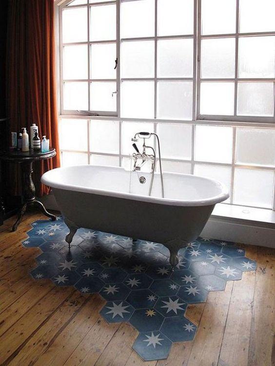 une salle de bain élégante avec un plancher en bois et une tuile hexagonale bleue avec un morceau de plancher d'étoiles sous la baignoire est magnifique