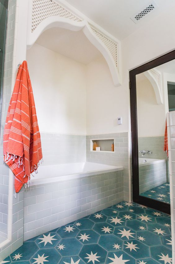 une salle de bains élégante et neutre revêtue de carreaux de métro blancs, d'appareils électroménagers blancs et d'un sol en carreaux hexagonaux en étoile bleue