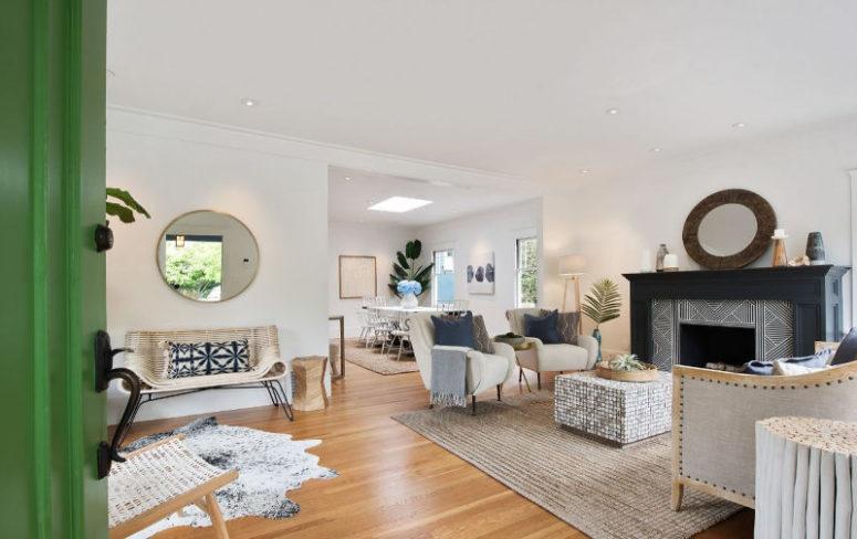 Le salon est neutre, avec un mobilier moderne chic du milieu du siècle, une cheminée revêtue de carrelage et plusieurs tapis