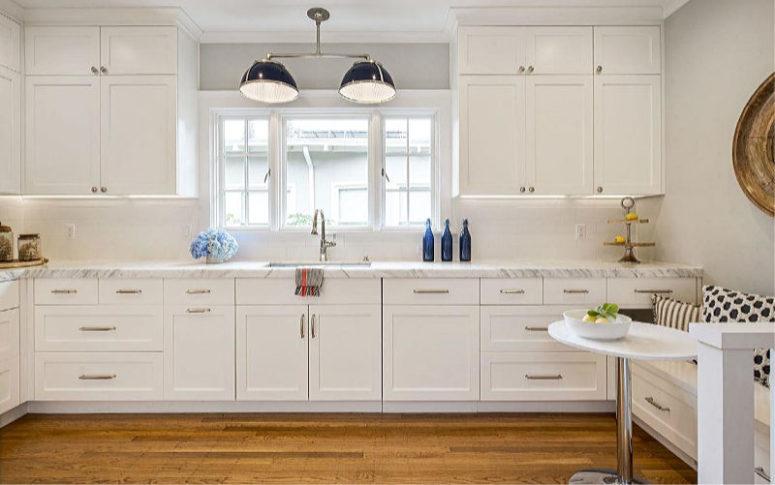 La cuisine est blanche, avec un comptoir en pierre et un petit coin petit-déjeuner confortable avec un siège intégré