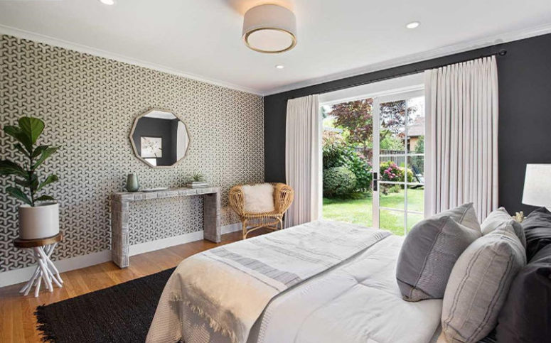 La chambre est faite avec un mur de papier peint imprimé, une porte vitrée donnant sur le jardin et des meubles élégants
