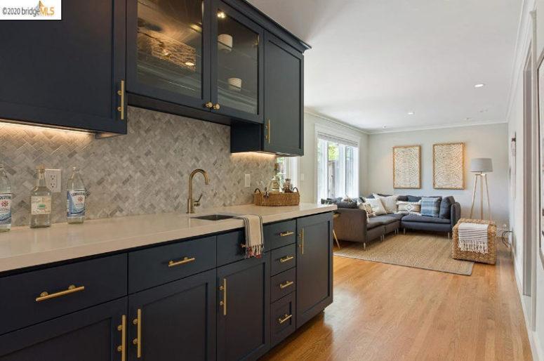 La zone inférieure comprend un bar et un espace de vie confortable avec un canapé d'angle gris graphite