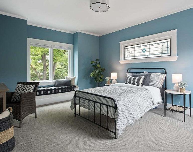 Une chambre d'amis est faite en bleu, avec plusieurs fenêtres, des meubles confortables en métal et en osier et des textiles monochromes
