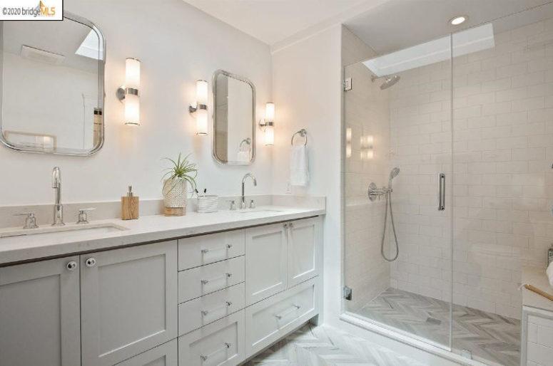 La salle de bain principale est faite dans des tons neutres, une double vasque et un espace douche
