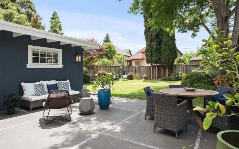 La cour arrière comprend une pelouse et un espace salle à manger et salon avec des meubles élégants et des plantes en pot