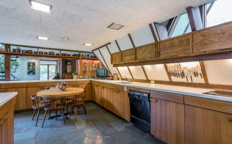 La cuisine est revêtue de bois et de pierre blanche, il y a plusieurs fenêtres et puits de lumière