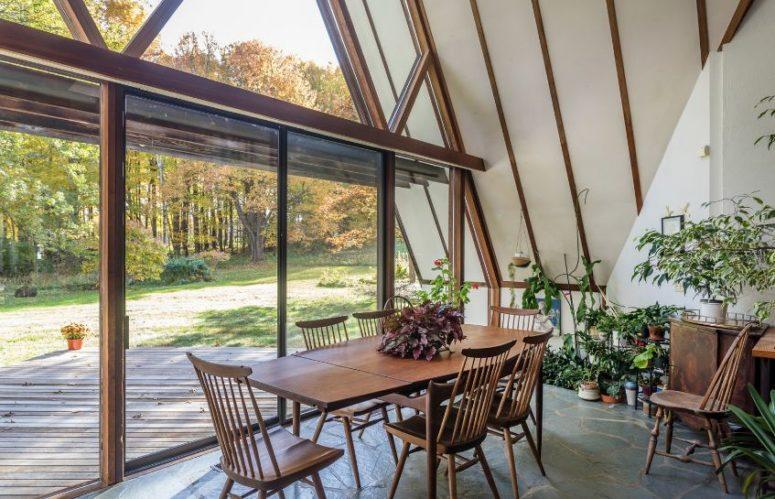 L'espace salle à manger est situé près d'un mur de verre, avec un ensemble de salle à manger en bois et de nombreuses plantes en pot