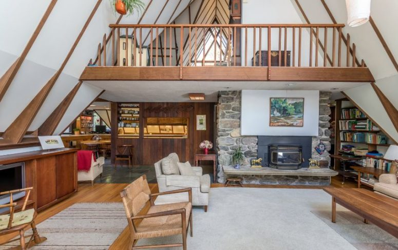 Le salon est neutre, avec une cheminée, des chaises tissées et des meubles confortables ainsi que des touches de bois