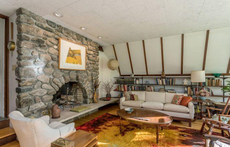Il y a un autre salon avec des murs blancs, une cheminée en pierre et des meubles modernes confortables du milieu du siècle