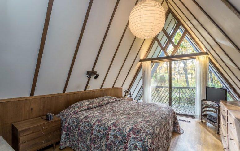Cette chambre dispose également d'un mur de verre, de meubles confortables et d'une lumière chaleureuse