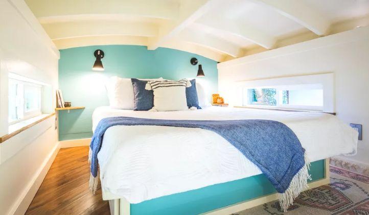 À l'étage, il y a une chambre avec de petites fenêtres, un mur d'accent turquoise et un grand lit confortable