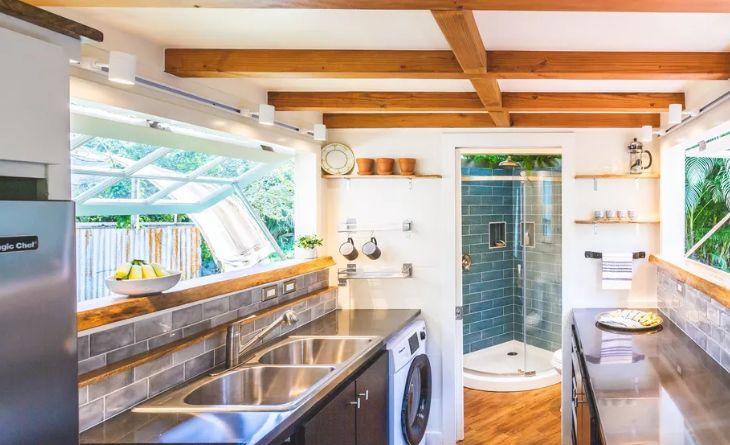 La cuisine comporte des fenêtres, des armoires noires et des poutres en bois au plafond