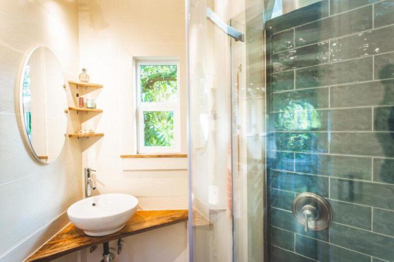 Une minuscule salle de bain comprend un petit lavabo dans le coin, une petite douche avec du carrelage
