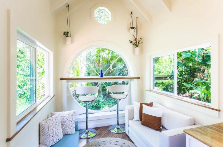 Le salon est fait avec une magnifique fenêtre ronde, un espace bar et deux petits canapés