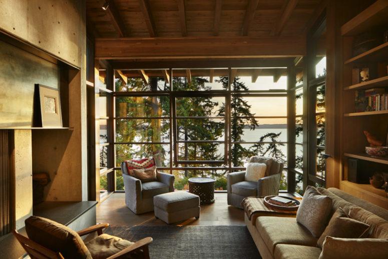 Le salon présente un mur vitré avec vue sur la forêt et la côte, une cheminée intégrée et un mobilier moderne