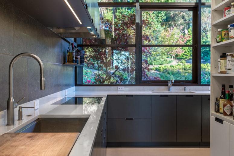 La cuisine est faite avec des armoires élégantes gris graphite, des comptoirs en pierre blanche et un mur vitré au lieu d'un dosseret