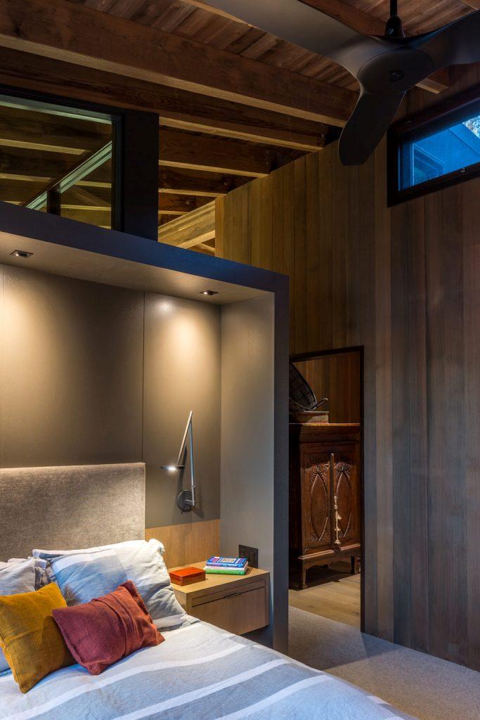 La chambre présente une niche avec un lit et des tables de nuit flottantes avec des appliques pour rendre le sommeil plus confortable