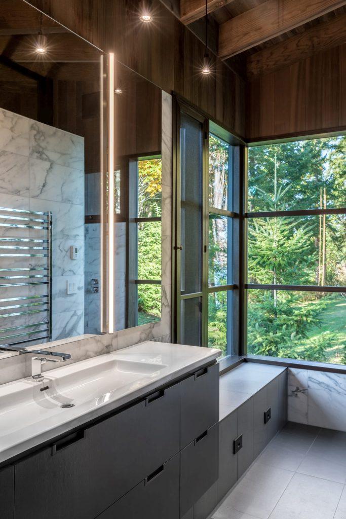 La salle de bain est faite avec des carreaux de marbre blanc et des armoires sombres et élégantes et une vanité, il y a aussi des murs vitrés ici