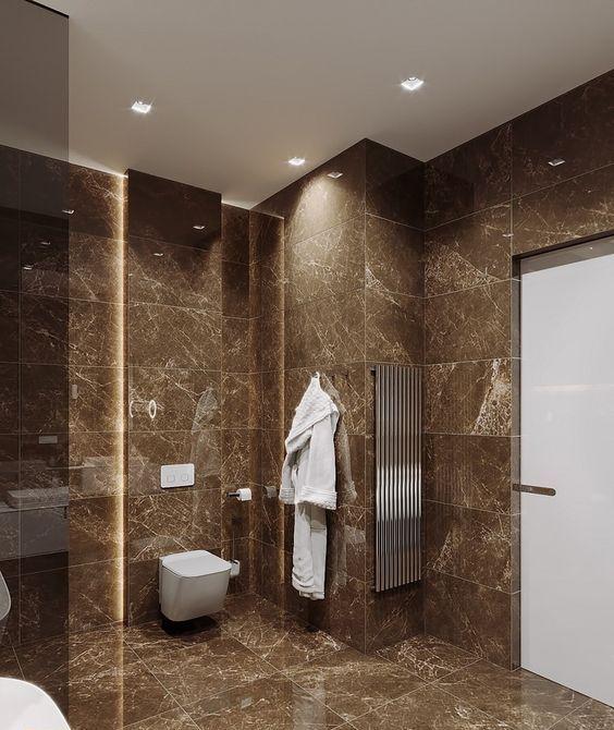 une salle de bain contemporaine marron revêtue de carreaux de marbre marron, avec des appareils blancs et des touches d'acier inoxydable