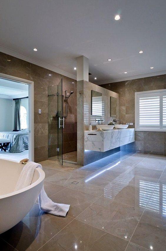 une grande salle de bain luxueuse avec des carreaux beige et marron, des lumières encastrées, des appareils électroménagers blancs et un meuble-lavabo en marbre