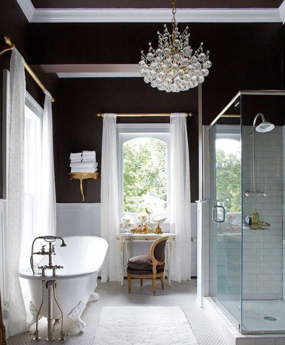 une salle de bain glamour avec des murs en chocolat, des lambris blancs, une baignoire vintage, un lustre en cristal chic et des meubles vintage épatant