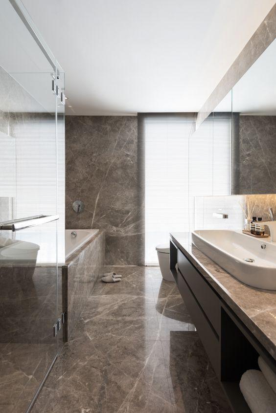 une salle de bain minimaliste revêtue de marbre brun, avec une vanité élégante en bois et une baignoire revêtue de marbre est chic