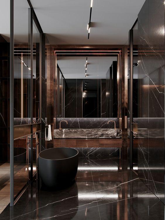 une salle de bain en marbre marron chocolat à couper le souffle avec un grand miroir, une baignoire noire et un espace douche
