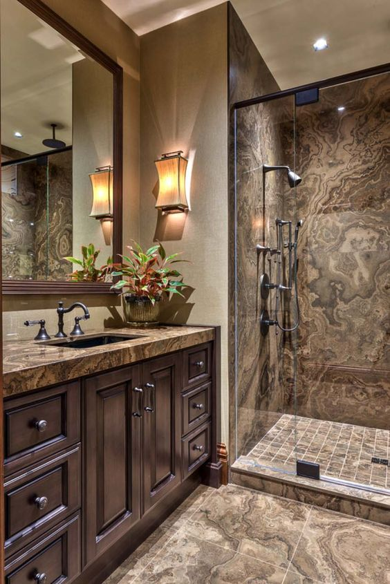 une salle de bain raffinée et fantaisiste dans les tons marron et taupe, avec des meubles et des luminaires vintage et des appliques accrocheuses