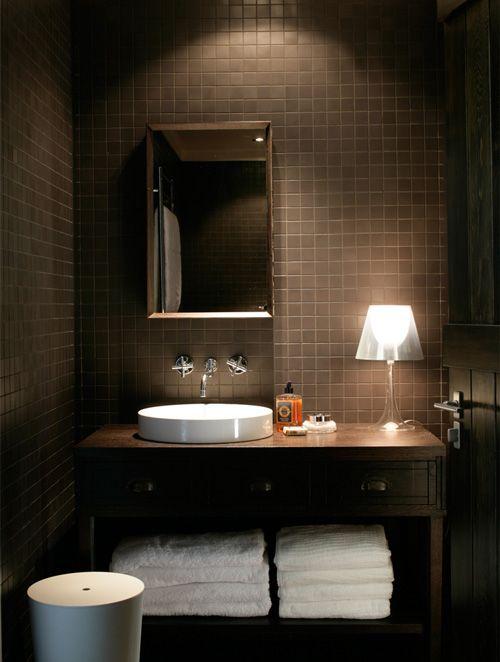 une salle d'eau chocolatée moderne avec du carrelage partout, une vanité en bois et des touches de blanc, des appareils électroménagers et des serviettes