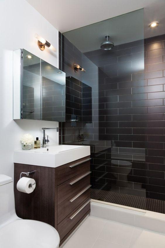 une salle de bains moderne brun chocolat et blanc avec des carreaux bruns dans la douche, une vanité marron et des appareils et des murs blancs