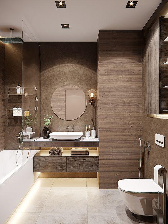 une salle de bain marron moderne revêtue de tuiles en bois, un meuble flottant et une unité de rangement, des appareils blancs