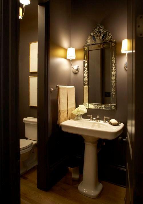 une élégante salle de bain marron avec un miroir vintage, un lavabo sur pied et des luminaires et luminaires vintage