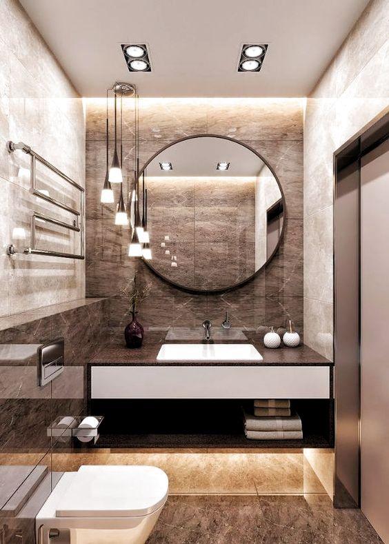 une salle de bain marron raffinée avec du carrelage, des luminaires encastrés, des suspensions et un miroir rond