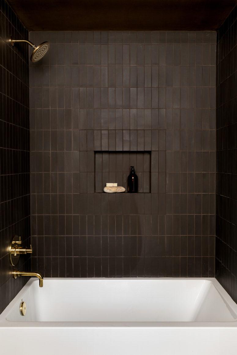 une salle de bain de mauvaise humeur raffinée revêtue de carreaux brun chocolat, avec des luminaires dorés chics, une baignoire blanche et une niche pour le rangement