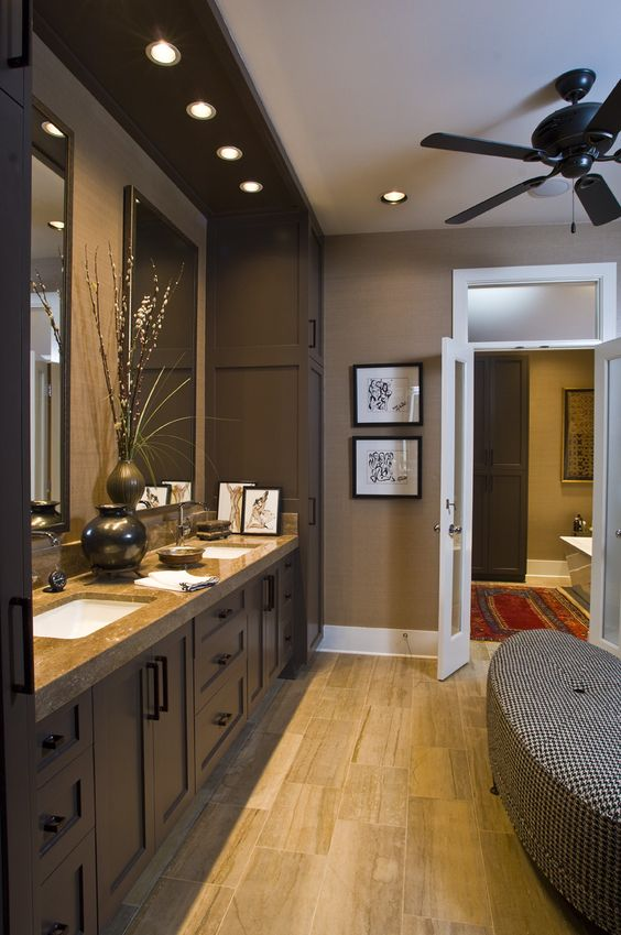 une élégante salle de bains marron avec des murs beige, des meubles marron chocolat, un comptoir en pierre et un banc rembourré imprimé