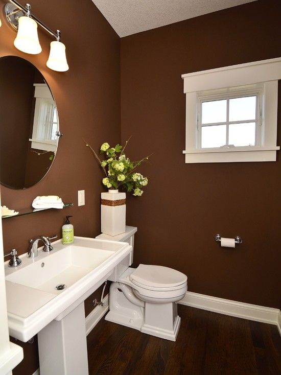 une élégante salle de bains marron avec des appareils et des lampes blancs et une atmosphère moderne du milieu du siècle