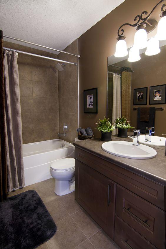 une salle de bain d'inspiration vintage faite avec des carreaux et des meubles bruns et rafraîchie avec des appareils blancs et une plante en pot