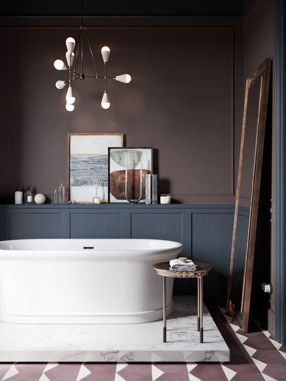 une salle de bain de mauvaise humeur super raffinée avec des murs brun chocolat, des boiseries grises, une baignoire chic sur une plate-forme en marbre et un miroir de sol