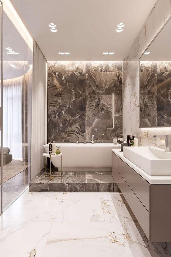 une salle de bain exquise faite de carreaux de marbre, de bronzage et de blanc, une baignoire sur une plate-forme et une longue vanité