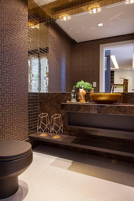 une élégante salle de bain marron avec des murs imprimés, un meuble-lavabo en pierre marron et des touches d'or pour un look glamour