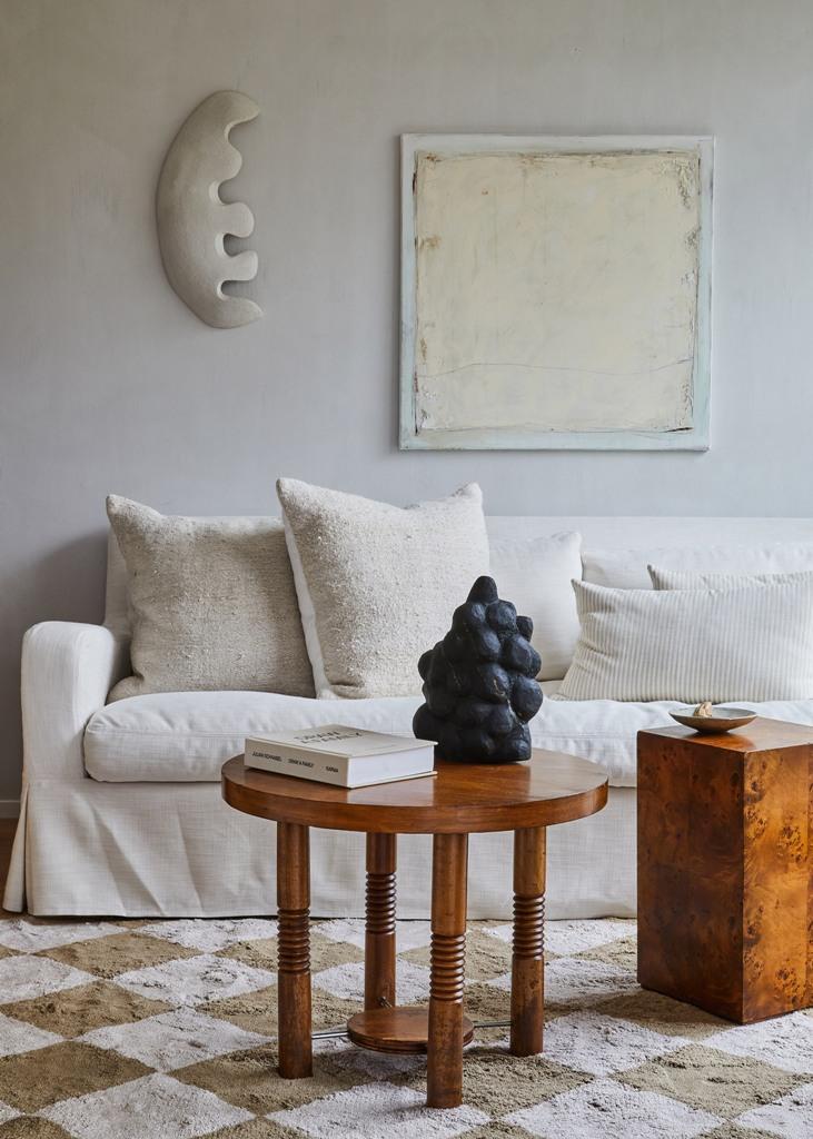 Le salon est fait avec un canapé blanc, une table en bois et quelques oreillers simples