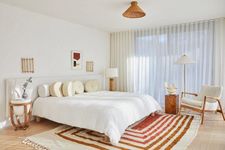 La chambre principale est moderne du milieu du siècle, principalement neutre mais avec un tapis à rayures et des touches d'osier et de pierre