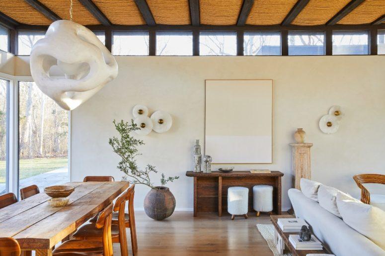 Le salon et les salles à manger sont réunis en un seul, les murs vitrés et les puits de lumière remplissent la disposition de lumière naturelle