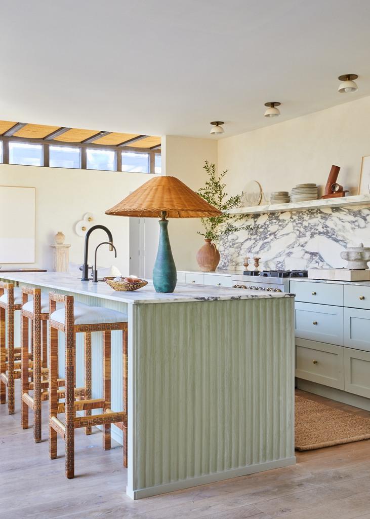La cuisine est vert menthe, les comptoirs et le dosseret sont en marbre blanc, et vous pouvez voir quelques articles en osier ici