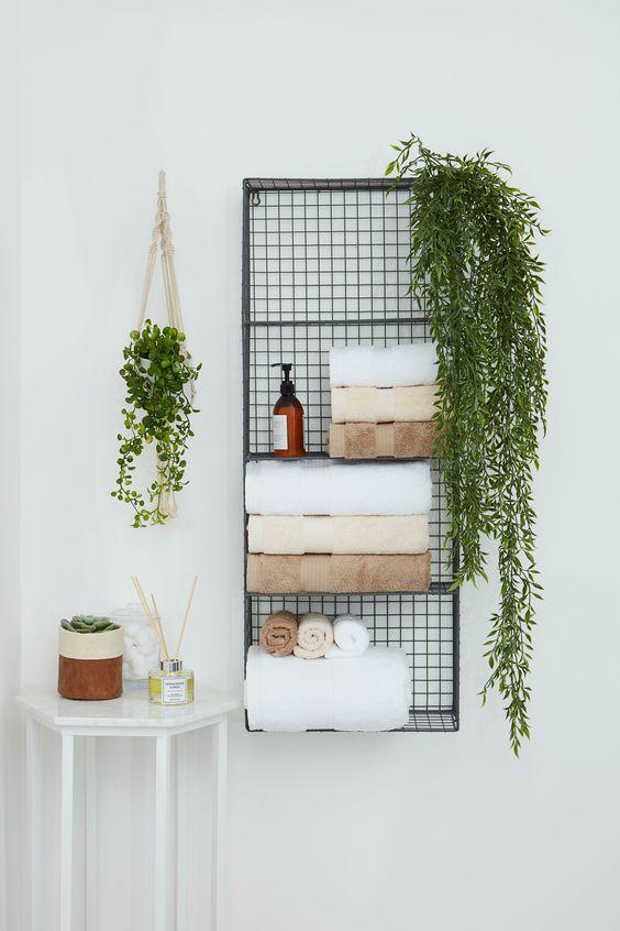 une étagère murale en métal pour ranger les serviettes, les savons, la verdure dans des pots est une belle solution pour économiser de l'espace au sol