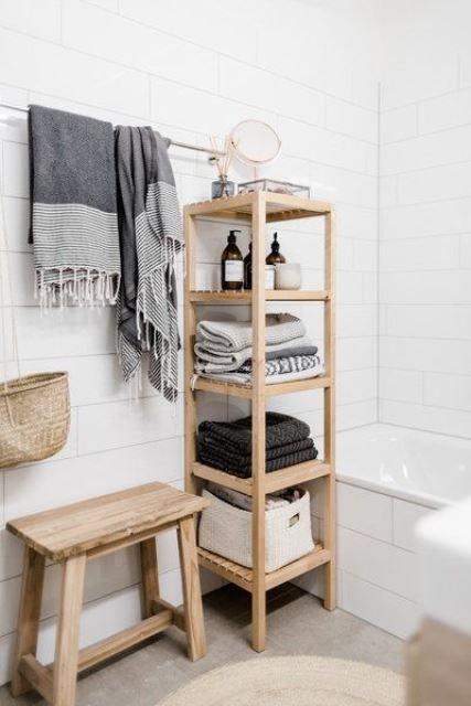une étagère en bois minimaliste avec des serviettes et divers articles de toilette nécessaires et une balustrade pour les serviettes au-dessus