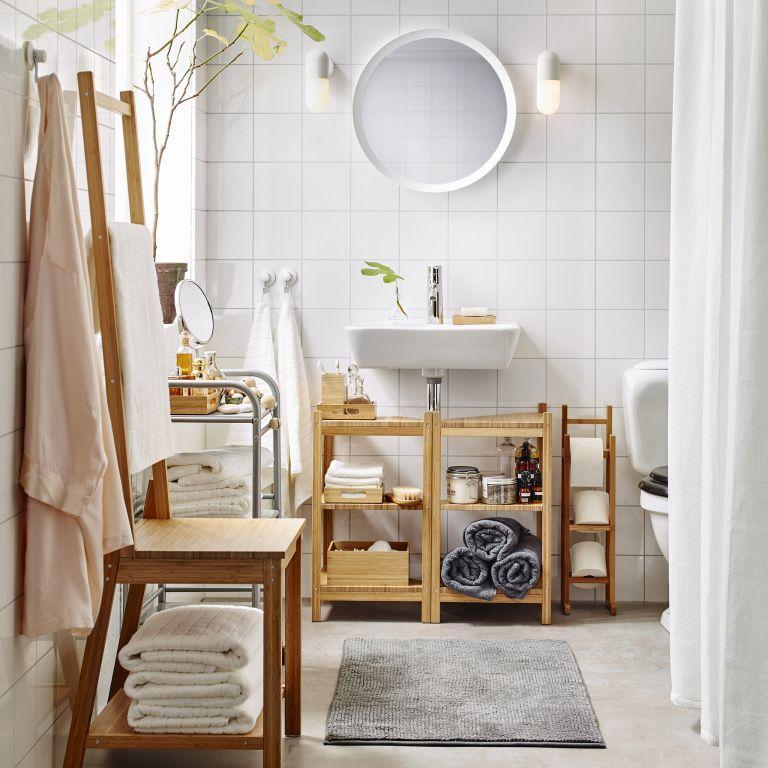 une salle de bain contemporaine chic faite dans des tons neutres et avec des meubles simples, avec des serviettes dans la vanité et à l'intérieur d'un tabouret
