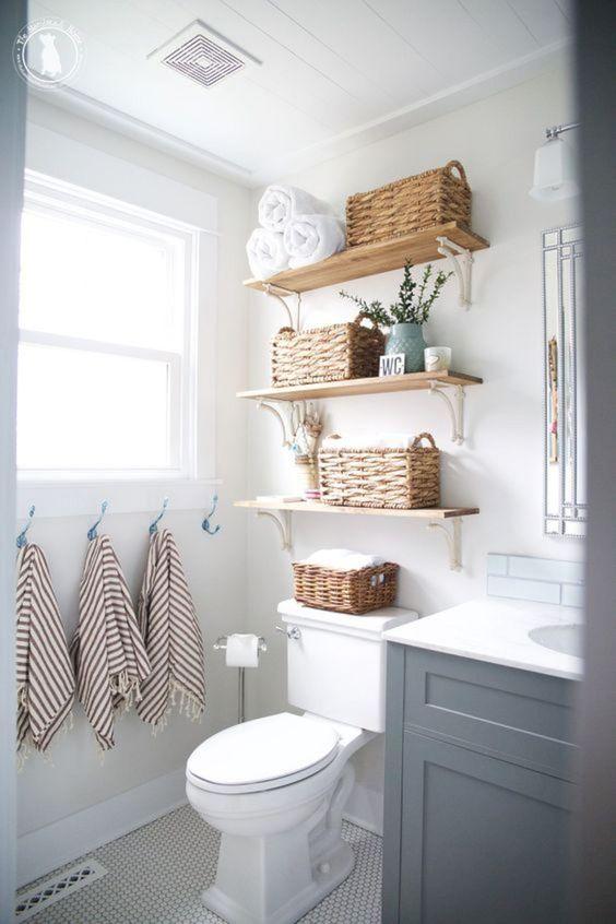 les étagères ouvertes avec des paniers peuvent ranger les serviettes confortablement et ici, elles prennent juste un peu d'espace au-dessus des toilettes